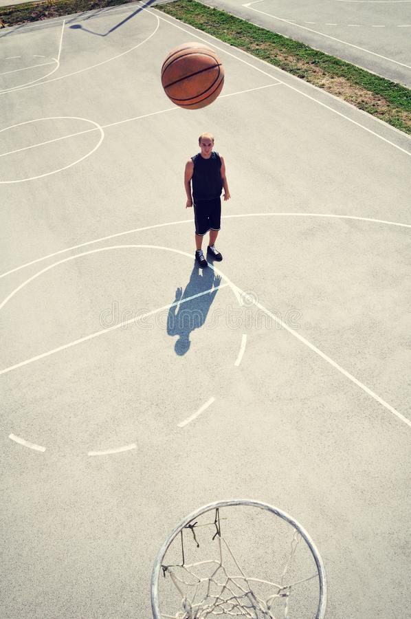 Basketball player at the court shooting the ball royalty free stock image