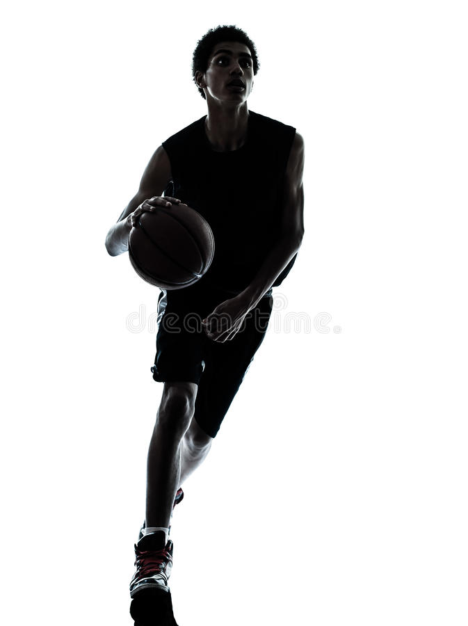 Basketball player dribbling silhouette. One young man basketball player dribbling silhouette in studio isolated on white background stock image