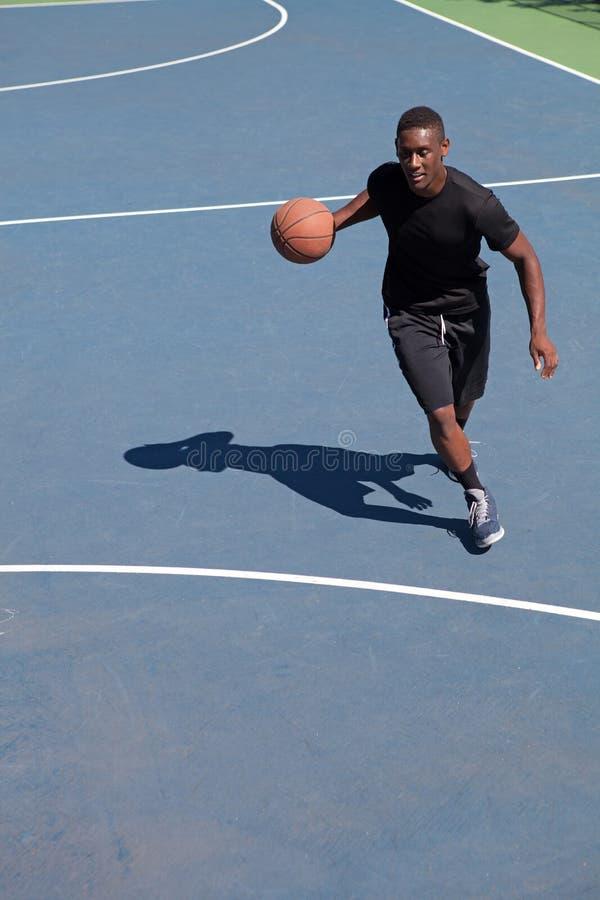 Basketball Player Dribbling. A sweaty young basketball player dribbling down the court demonstrating his ball handling skills royalty free stock photography