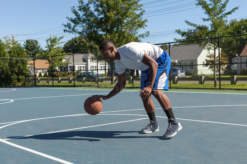Basketball Player Dribbling. A sweaty young basketball player dribbling down the court demonstrating his ball handling skills stock images
