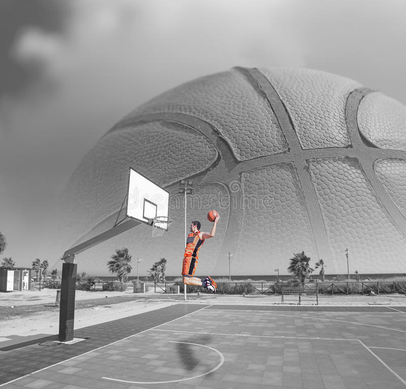 Basketball player dunking by the sea royalty free stock photos