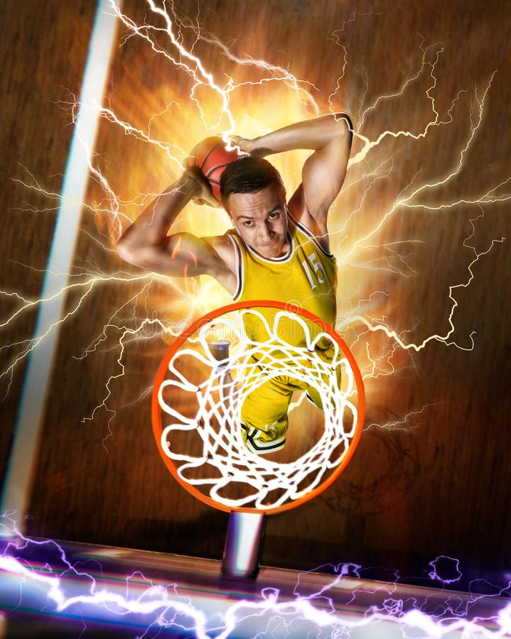 Basketball player in fire making slam dunk on basketball arena stock image