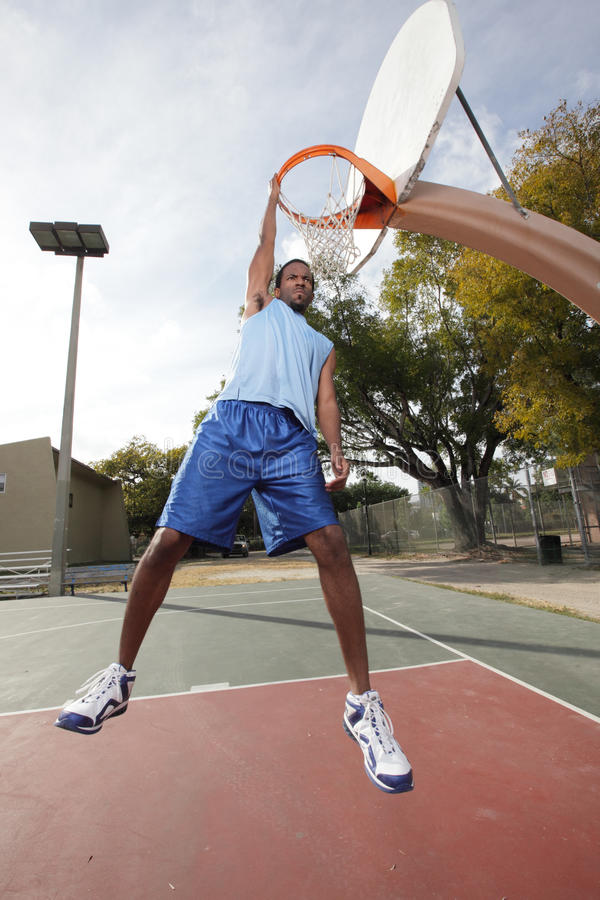 Basketball Player Hanging From The Hoop Royalty Free Stock Photography