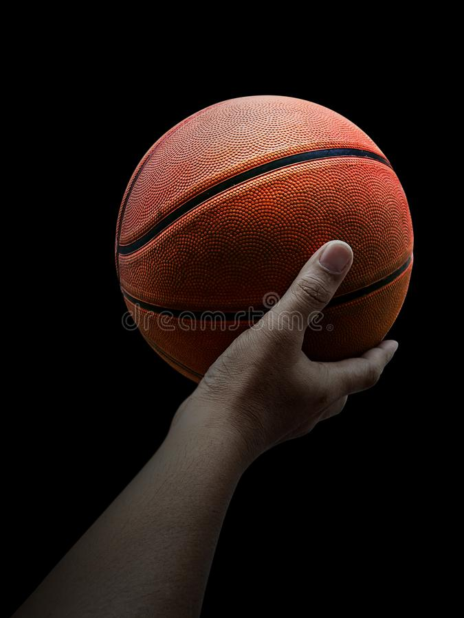 Basketball player holding a ball against black background. For design In the media Advertising royalty free stock photo
