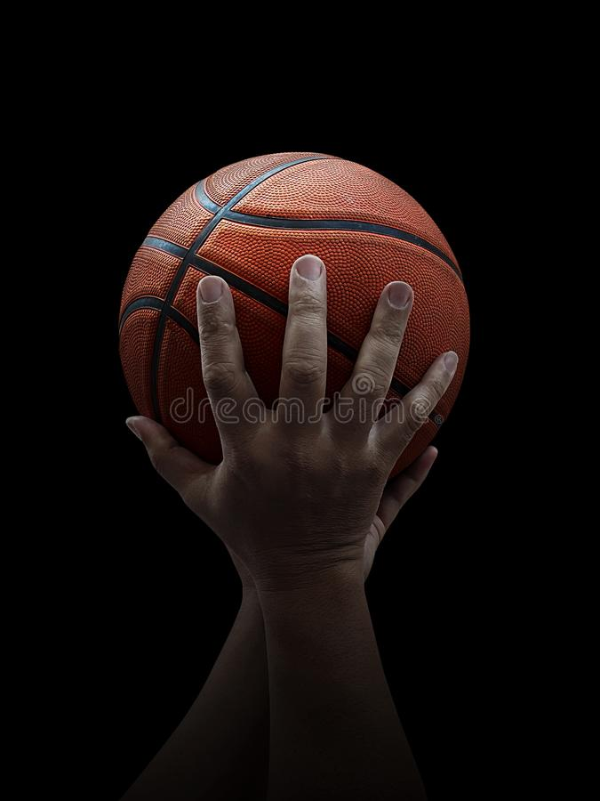 Basketball player holding a ball against black background. For design In the media Advertising royalty free stock photography