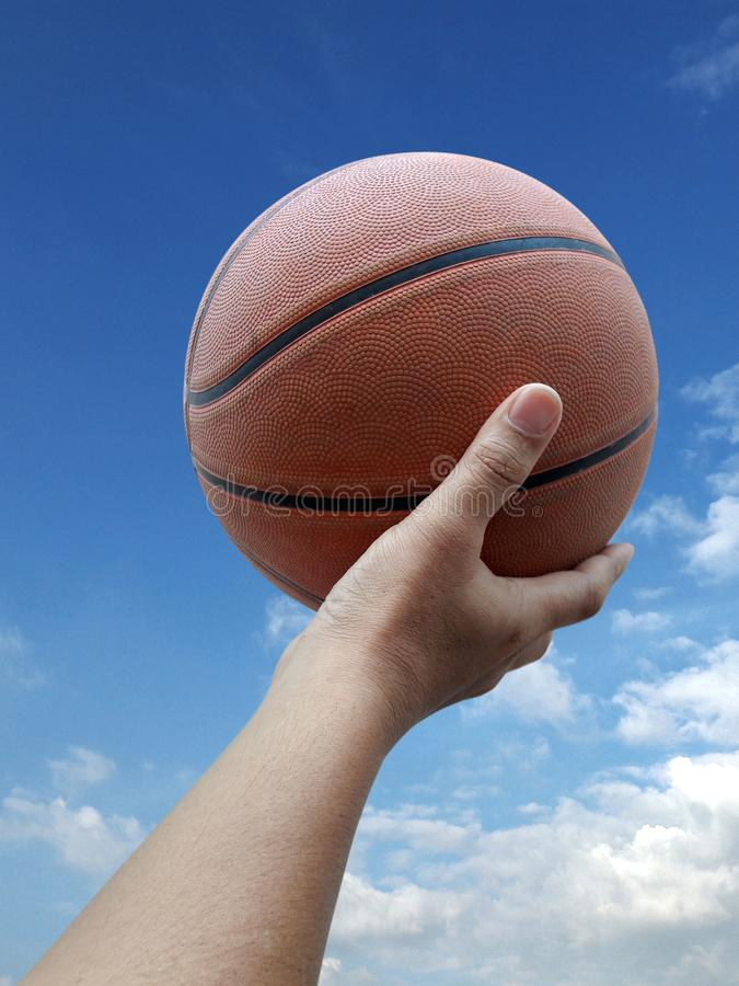 Basketball player holding a ball against sky background. For design In the media Advertising royalty free stock photography