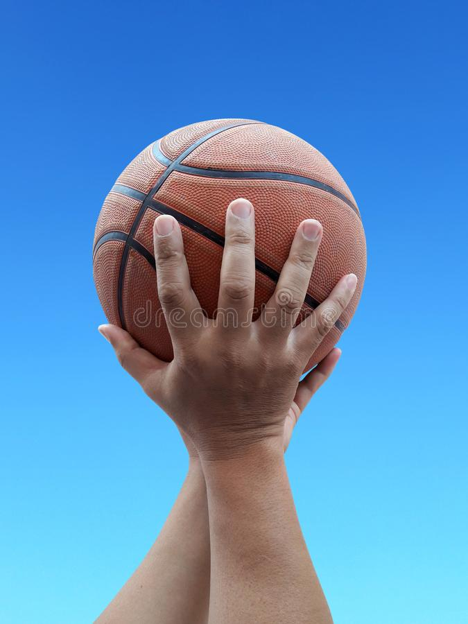 Basketball player holding a ball against sky background. For design In the media Advertising stock images