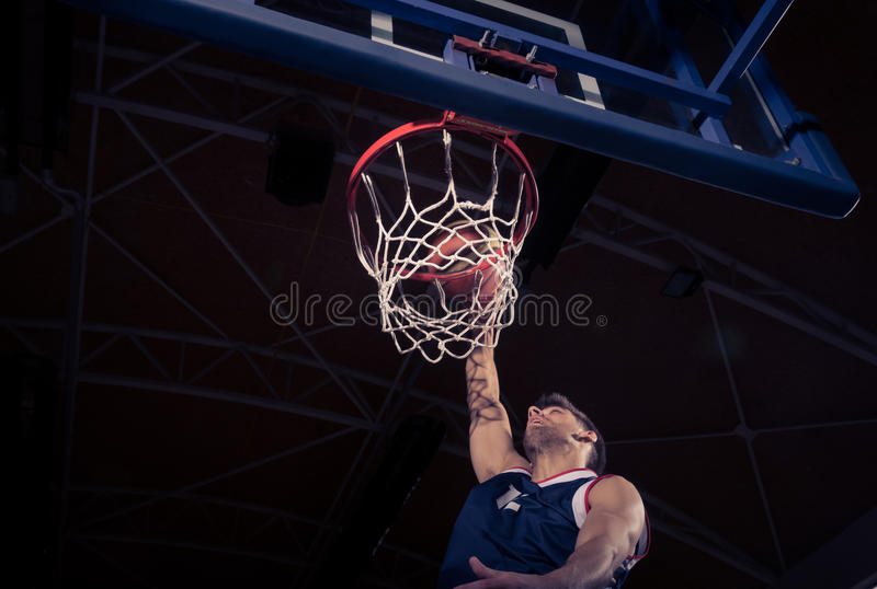 Basketball player, low angle view, slam dunk. One young adult man, basketball player, one hand, net rim, low angle view, slam dunk, dark indoors royalty free stock photos