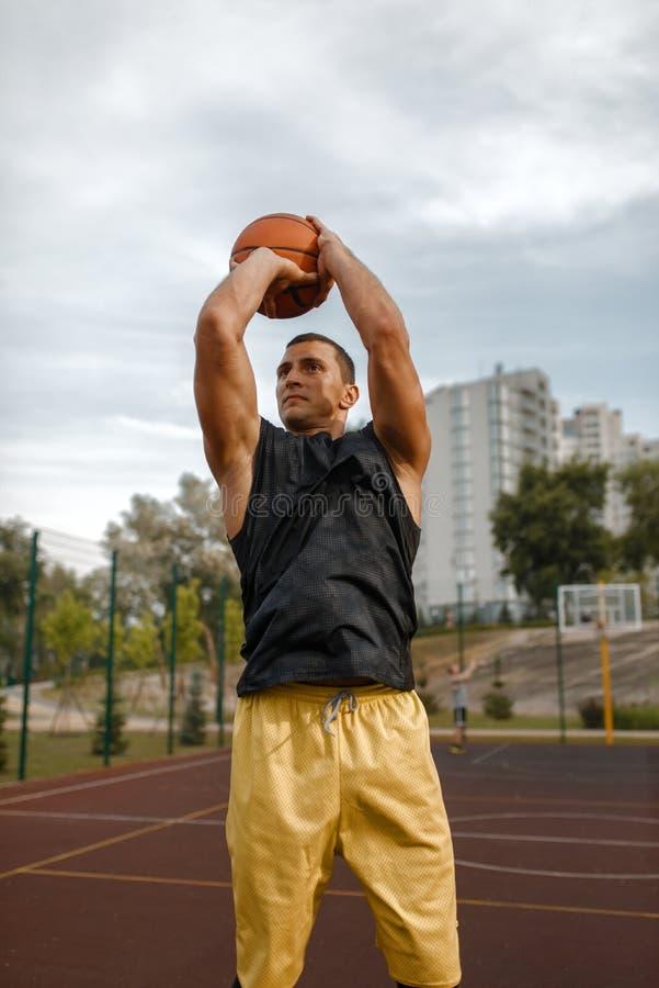 Basketball player makes a throw on outdoor court stock photos
