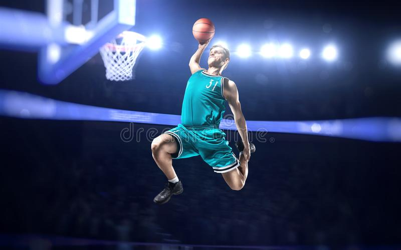 Basketball player making slam dunk on basketball arena. Lights background stock photo