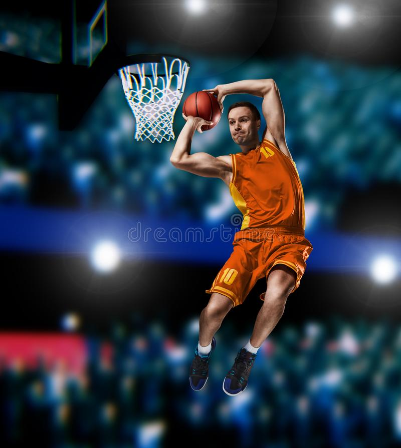 Basketball player making slam dunk on basketball arena. Lights background stock images