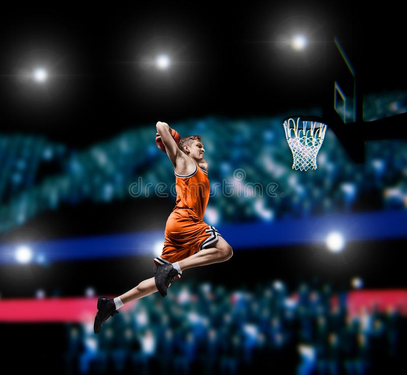 Basketball player making slam dunk on basketball arena. Lights background royalty free stock image