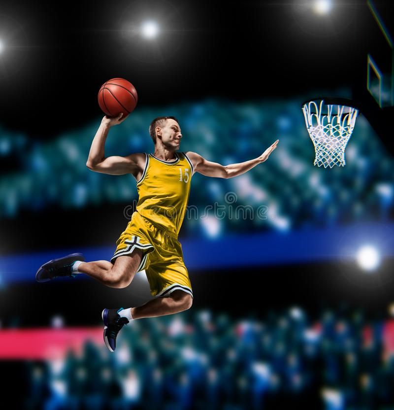 Basketball player making slam dunk on basketball arena. Lights background royalty free stock photos
