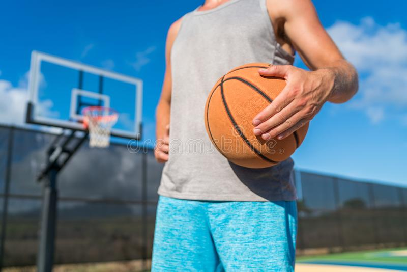 Basketball player holding ball at court net stock images