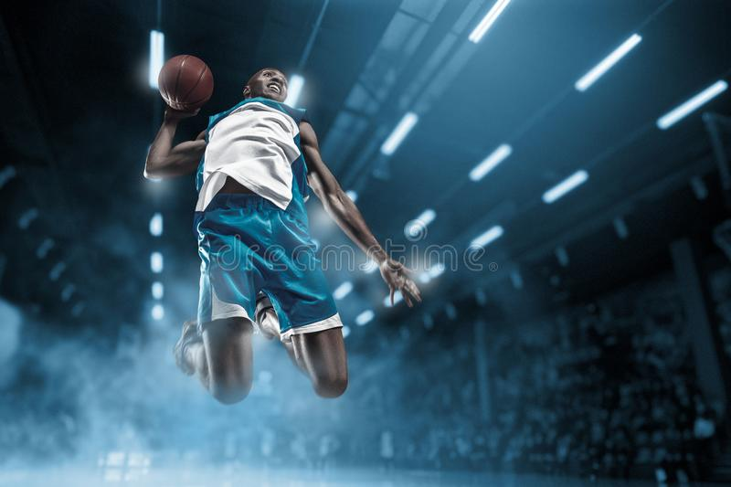 Basketball player on big professional arena during the game. Basketball player making slam dunk. Basketball player in motion or movement on big professional stock images