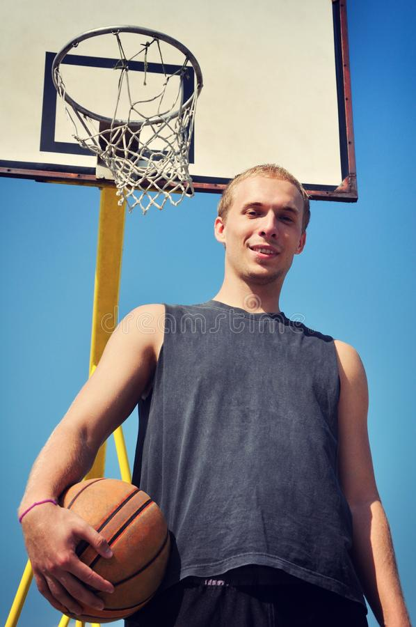 Basketball player posing and smiling under the backboard stock images