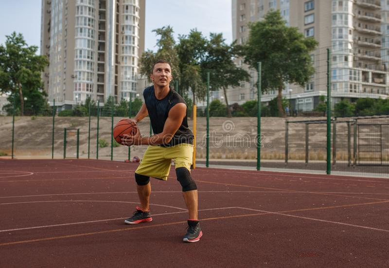 Basketball player prepares to make a shoot outdoor. Basketball player prepares to make a shoot on outdoor court. Male athlete in sportswear holds ball on stock photos