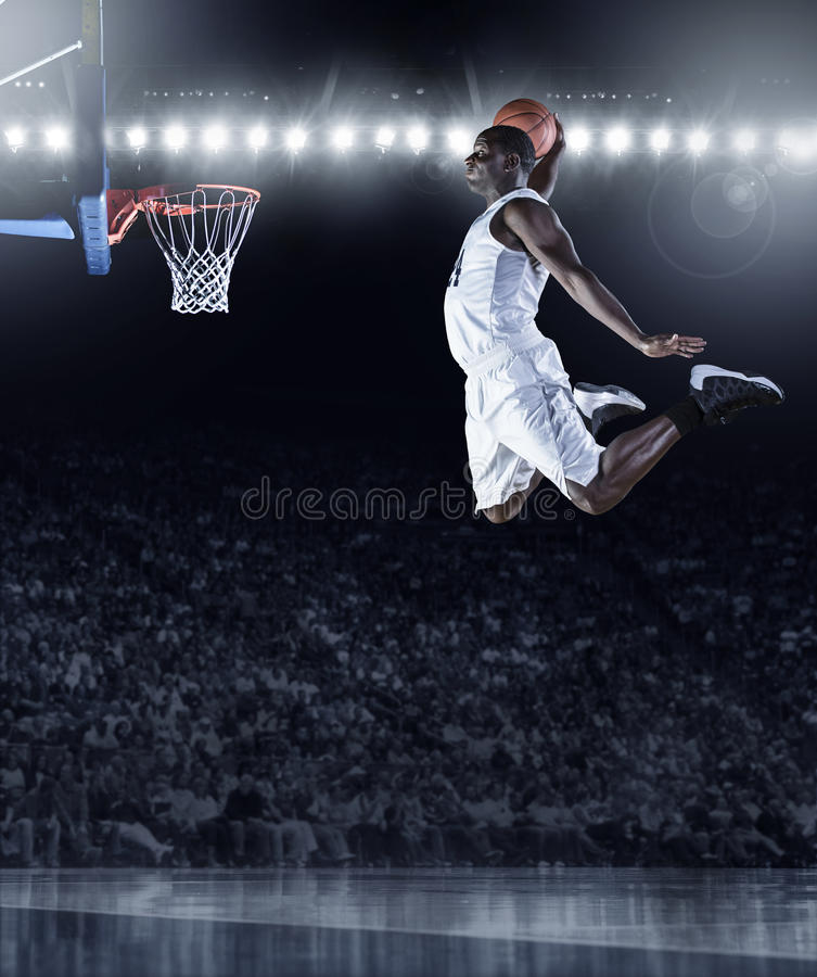 Basketball Player scoring an athletic, amazing slam dunk. The side view of an african american basketball player scoring an amazing slam dunk in a professional stock photography
