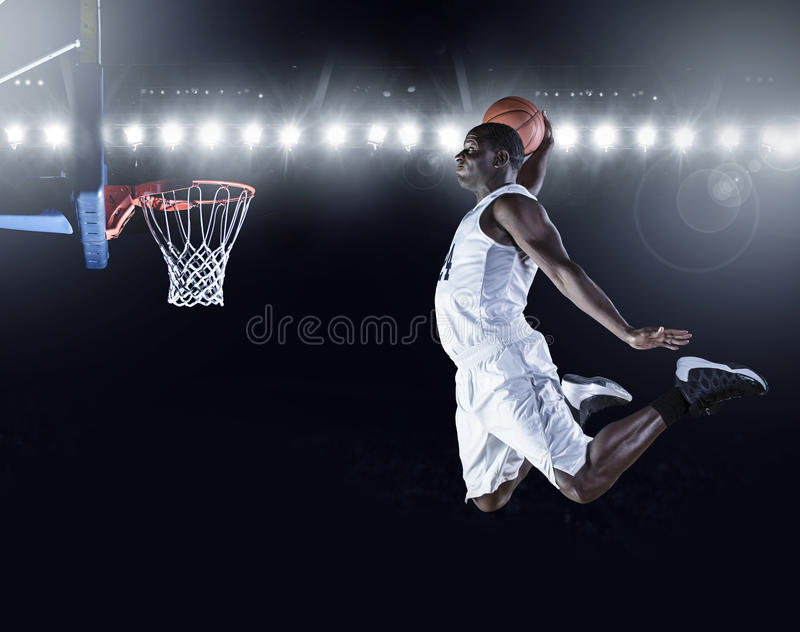Basketball Player scoring a slam dunk basket. An Athletic African American Basketball Player jumping high and scoring a slam dunk basket. High detail on a dark royalty free stock photography