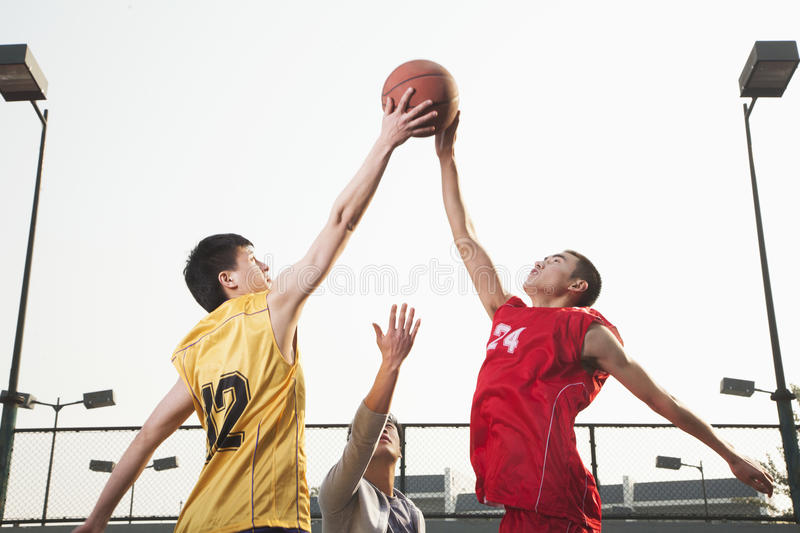 Basketball players fighting for a ball stock image