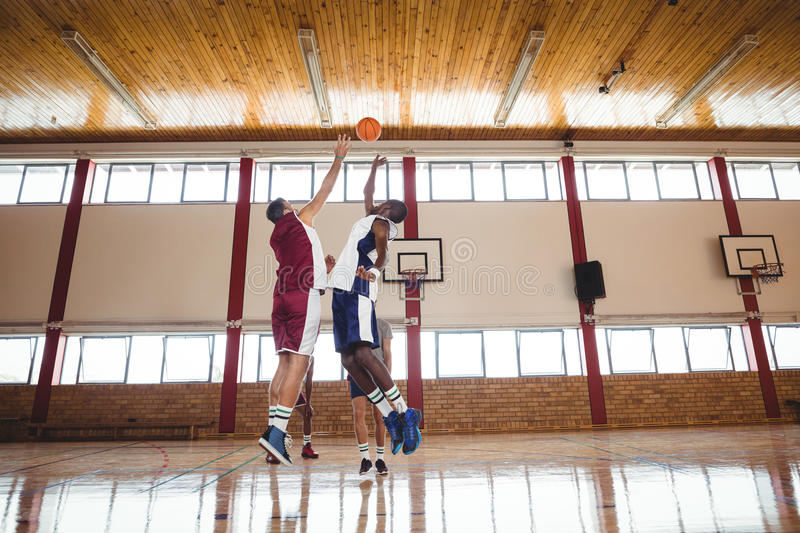 Basketball players playing basketball in the court stock images