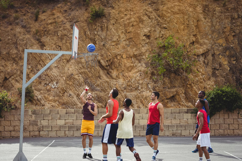 Basketball players playing basketball in the court royalty free stock photo