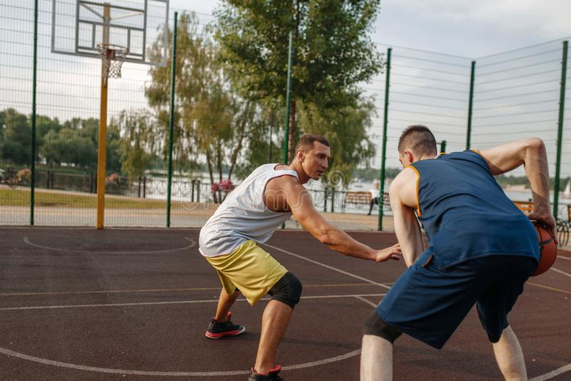 Basketball players playing intense match outdoor. Two basketball players playing intense match on outdoor court. Male athletes in sportswear play the game on royalty free stock photography