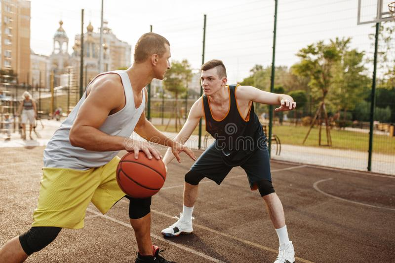 Basketball players playing intense match outdoor. Two basketball players playing intense match on outdoor court. Male athletes in sportswear play the game on stock photo