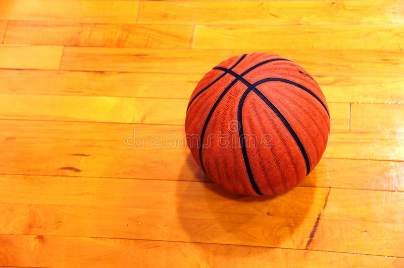 Basketball Practice. Worn basketball sits on gym floor. Ball is faded and worn from many pre-game pracices and warm ups stock images