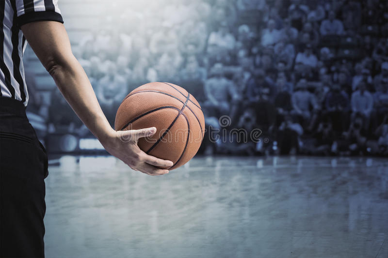Basketball referee holding ball at a basketball game during a timeout. A basketball referee holding a basketball at a game in a crowded sports arena. Holding the stock image