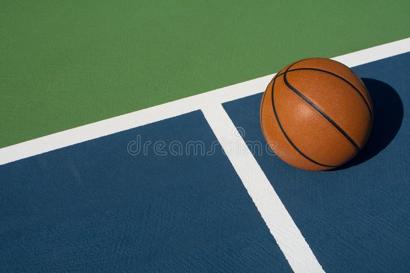 Basketball rests on court. Leather basketball on colorful outdoor court - great background for your hoops related event stock photos