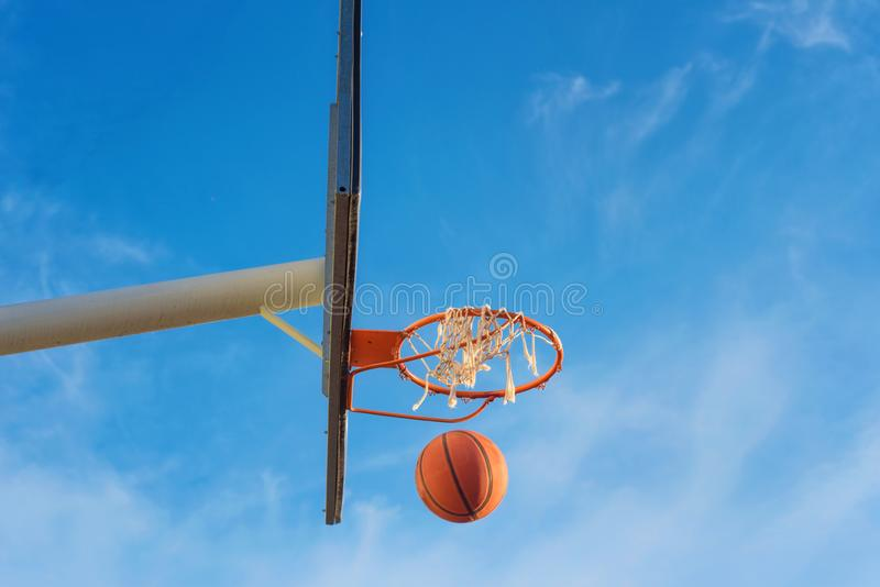 Basketball shield, ball flying to basket on blue sky background stock image