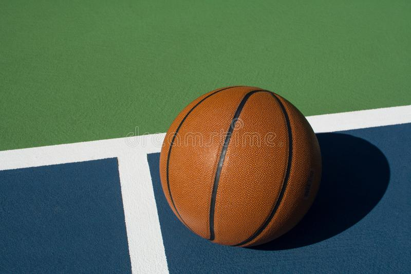 Basketball sits on court. Leather basketball on colorful outdoor court - great background for your hoops related event stock photography