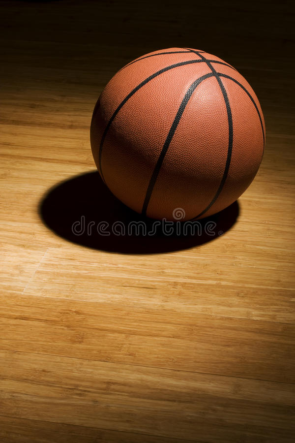 Basketball sitting on wood floor royalty free stock photo