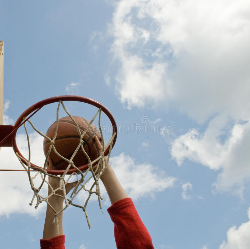 Basketball slam dunk. Hands young boy making basketball shot dank on clouds and blue sky backgrounds royalty free stock photo
