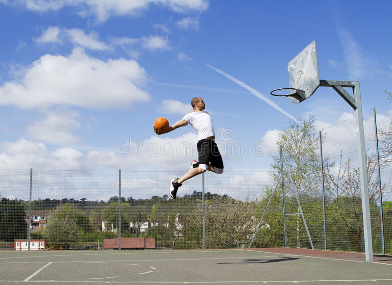 Basketball Slam Dunk. Male jumping up to slam dunk stock photos