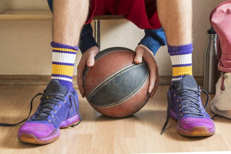 Basketball-Spieler im Umkleideraum auf der Bank, die den Ball f hält lizenzfreies stockfoto