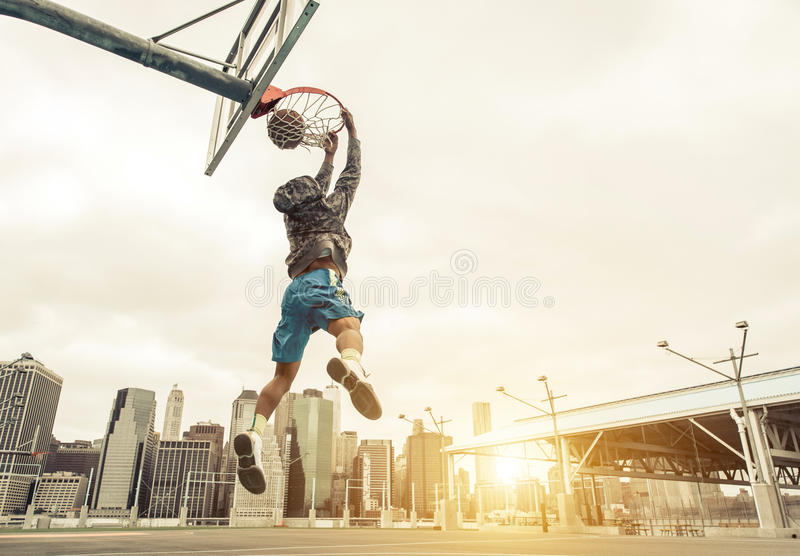 Basketball street player making a rear slam dunk. New york and Manhattan buildings in the background royalty free stock photos