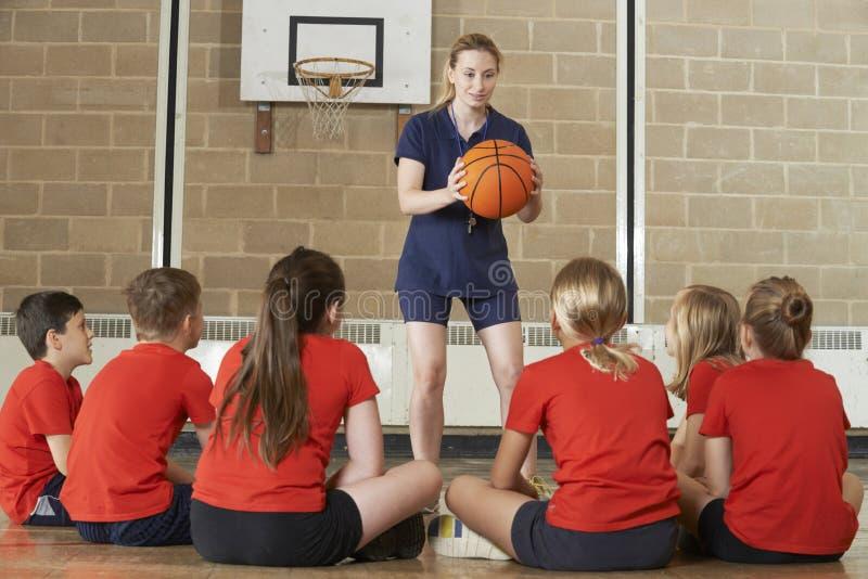 Basketball-Team Trainer-Giving Team Talk To Elementary School stockbilder