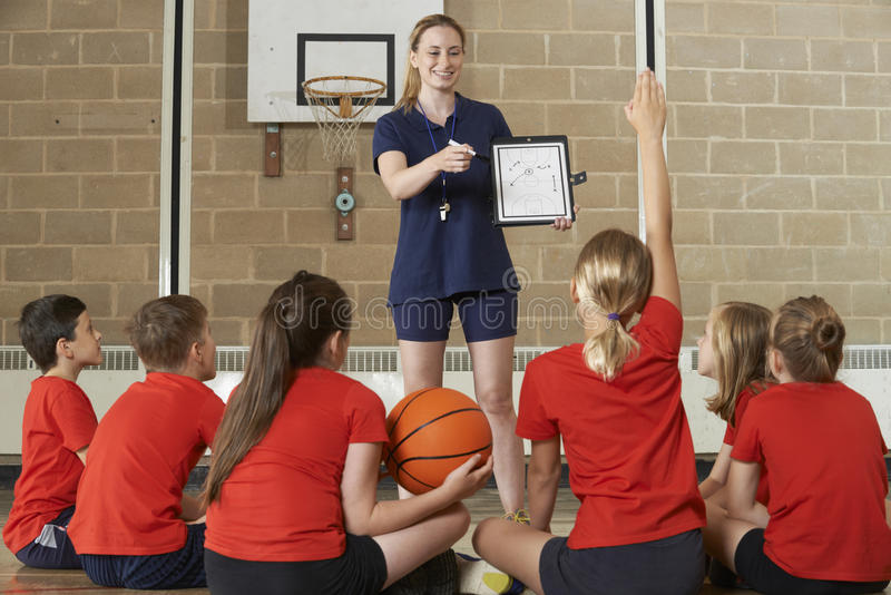 Basketball-Team Trainer-Giving Team Talk To Elementary School lizenzfreie stockfotografie