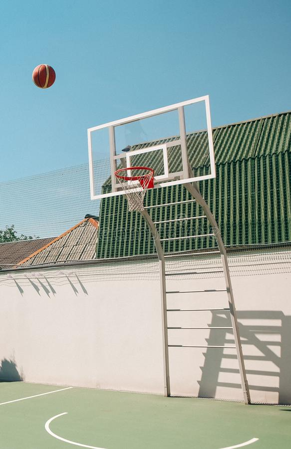 Basketball three points throw ball flight hit goal. Basketball three points throw the ball in flight hit a goal in the net, shot, template, sport, player, action royalty free stock image