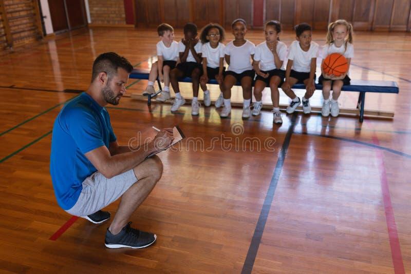 Basketball-Trainers-Schreiben auf Klemmbrett und Schulkinder, die auf Bank am Basketballplatz sitzen stockbilder