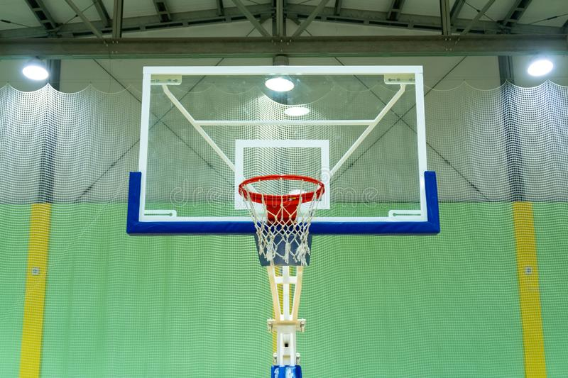 Basketball transparent backboard with basket in the gym. Green background. Sports theme. Copy space. Lanterns on the ceiling stock photo