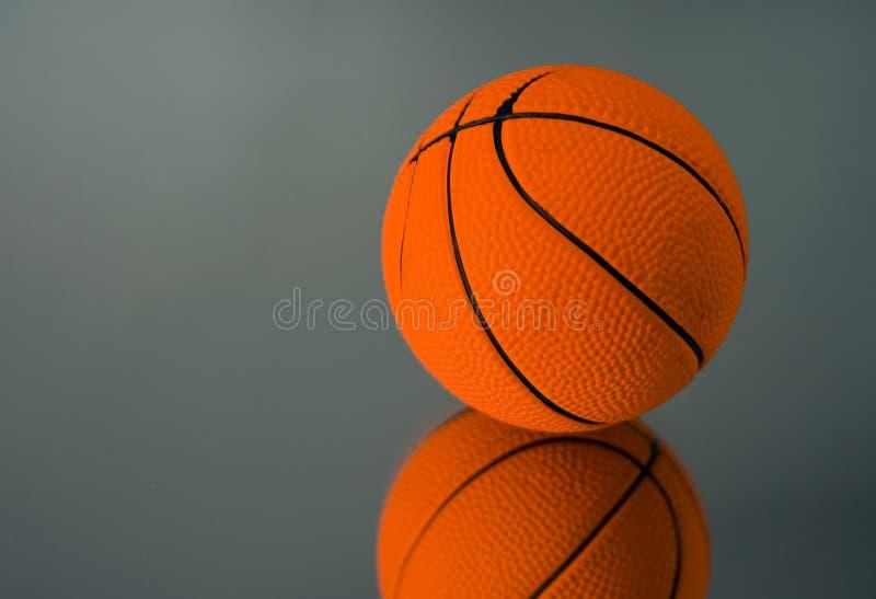 Basketball twins. Basketball on mirror surface (studio shot stock images