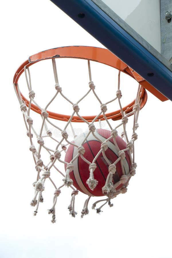 Basketball victory, a ball in a basket ring and net in motion blur royalty free stock photos
