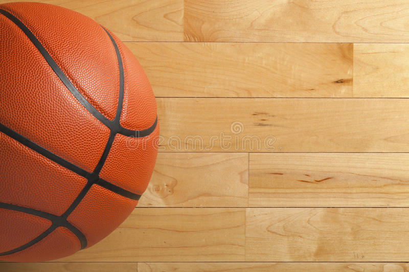 Basketball on wood gym floor viewed from above. A basketball on a wood gym floor viewed from above royalty free stock photos