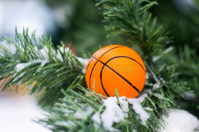 Basketballballspielzeug auf den Niederlassungen eines künstlichen Tannenbaums lizenzfreie stockfotos