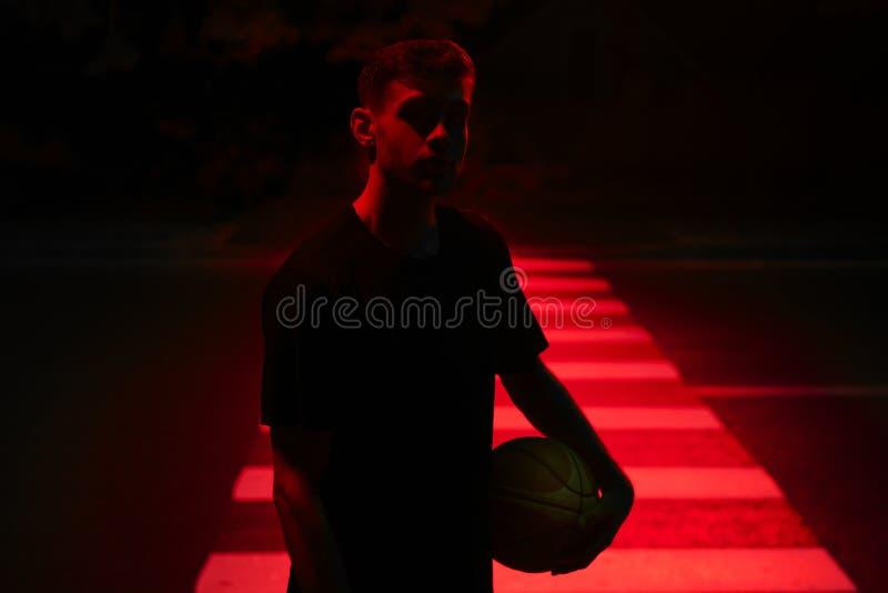 Basketballer joven del deportista en la luz roja del contraste imagen de archivo libre de regalías