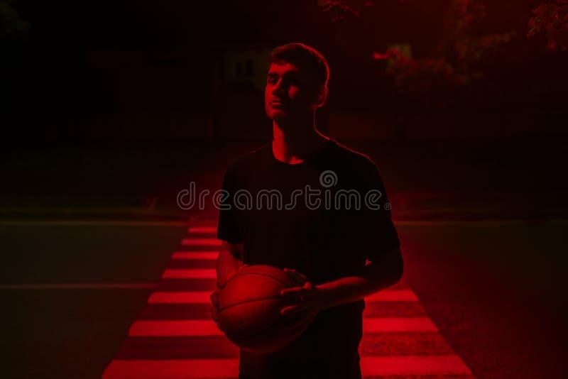 Basketballer joven del deportista en la luz roja del contraste fotos de archivo