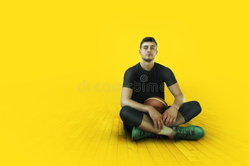 Basketballer novo do desportista na luz vermelha do contraste fotografia de stock royalty free